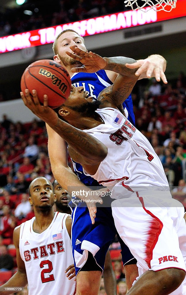 D.J. Cunningham #33 of the North Carolina-Asheville Bulldogs fouls Richard Howell #1 of the North Carolina State Wolfpack on a drive to the basket during play at PNC Arena on November 23, 2012 in Raleigh, North Carolina. North Carolina State won 82-80.