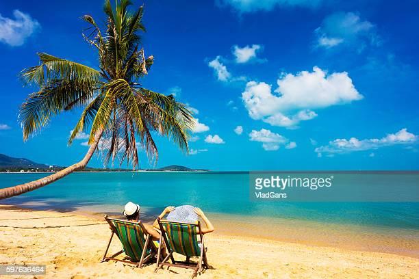Cuople sentado en una silla de playa