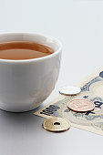 Cup and Japanese currency on white background, close-up