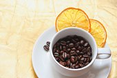 Cup and saucer, coffee beans, slices of dried orange on a gold background. A white cup and saucer with roasted coffee beans, with two pieces of dried orange and a couple of coffee beans on the saucer