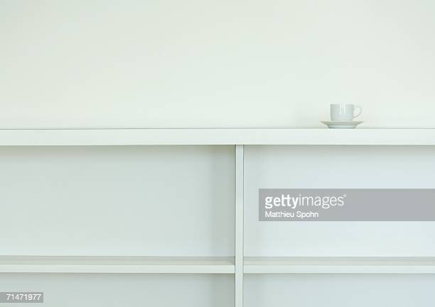 Cup and saucer on top of empty bookcase