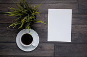 Cup coffee on wooden background with empty note, top view