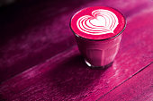 Cup of hot beetroot latte coffee is standing on the painted wooden background. Trendy healthy drink