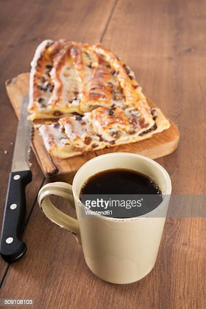 Cup of black coffee, knife and Danish pastry with marzipan on wooden board and table