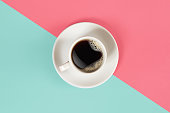 A cup of black coffee on blue and pink background. View from above. Still life. Mock up. Flat lay. Copy space