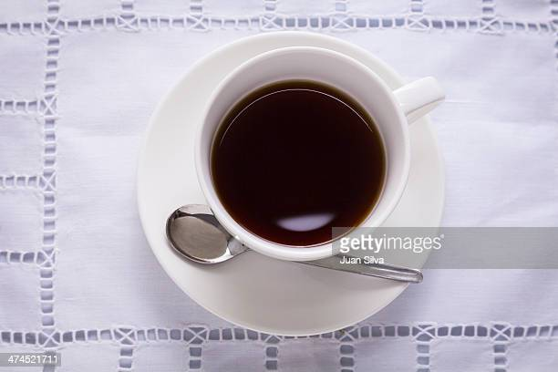 Cup of black coffee on white table cloth
