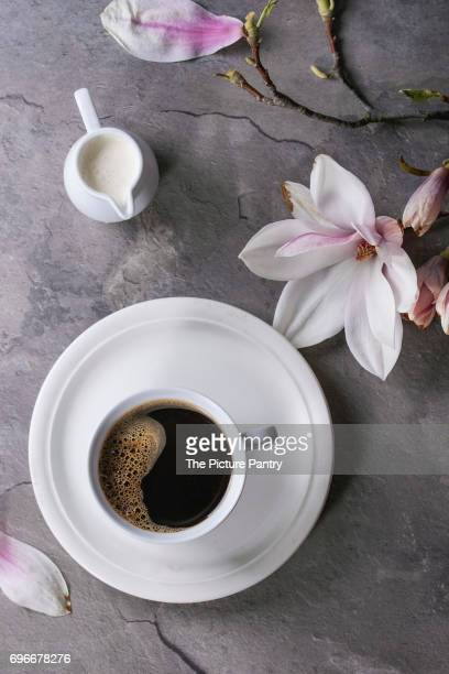 Cup of black coffee with magnolia
