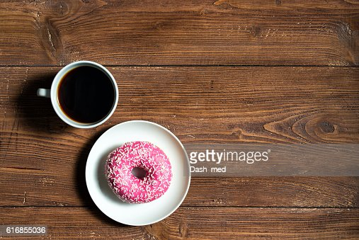 Cup of black coffee with pink donut on wooden background : Stock Photo