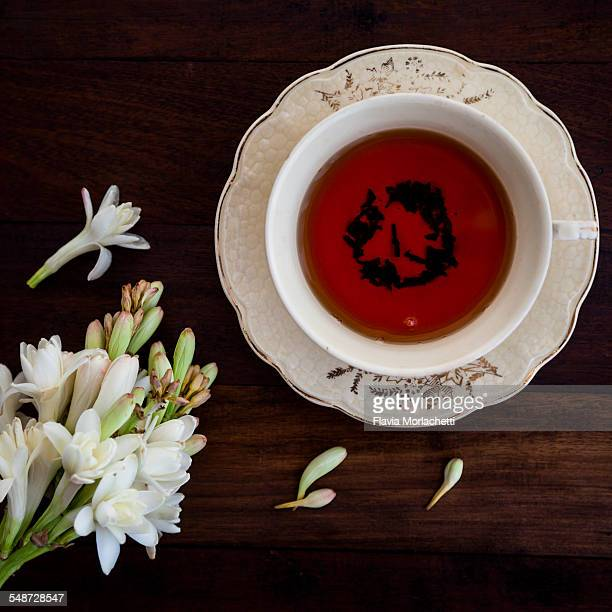 Cup of black tea and white flowers