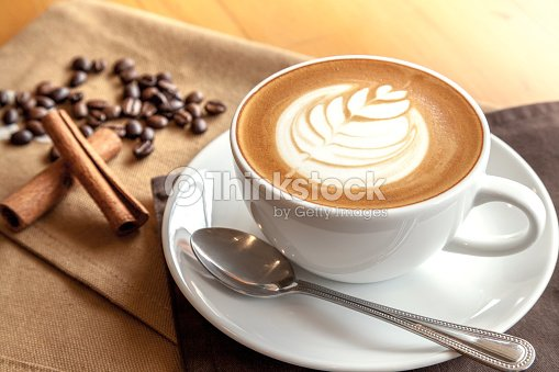 Cup of cafe' latte with coffee beans and cinnamon sticks : Stock Photo