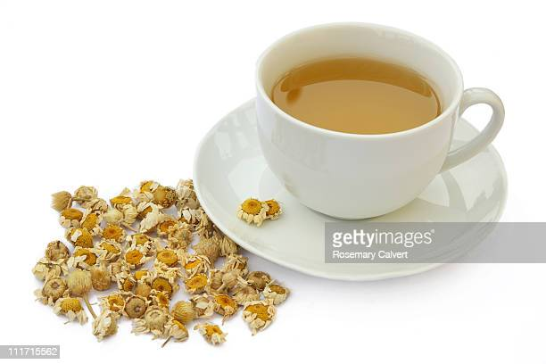 Cup of camomile tea with dried camomile flowers.