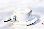 cup of cappuccino on table in outdoor setting