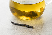 Glass cup of natural Chinese Kuding needle tea close up
