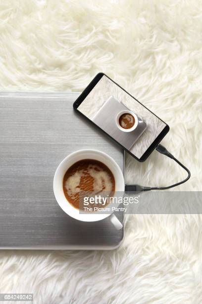 A cup of coffee and a cell phone connected to laptop. Image displayed on smartphone