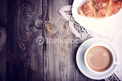 Cup of coffee and a croissant on a saucer