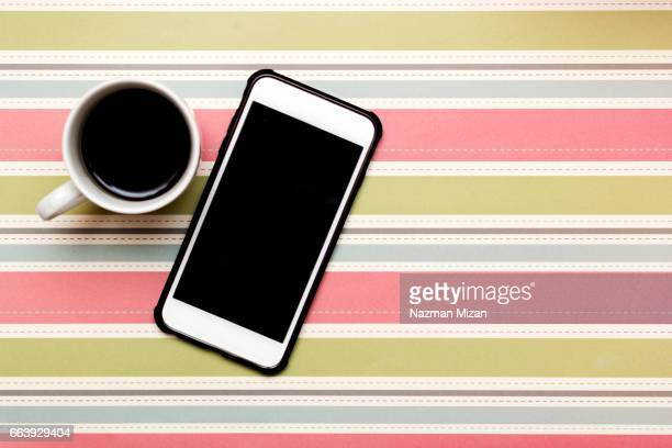 A cup of coffee and a smart phone on colorful background.