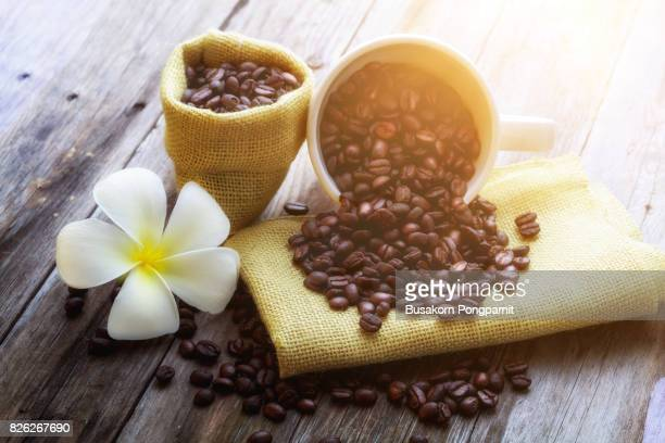 Cup of coffee and coffee beans on old wooden table