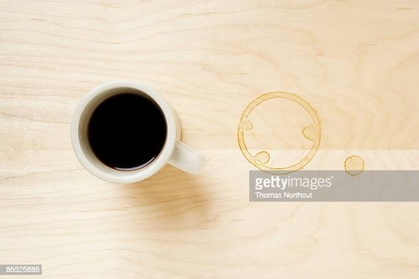 Cup of coffee and coffee ring on table.