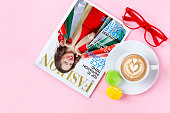 Cup of coffee, colorful macaroons and fashion magazine on pastel pink background.