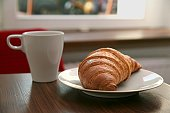 Cup of coffee and croissant on table