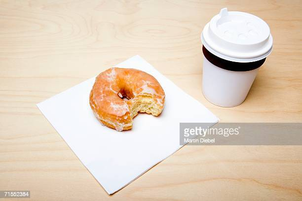 Cup of coffee and donut with missing bite