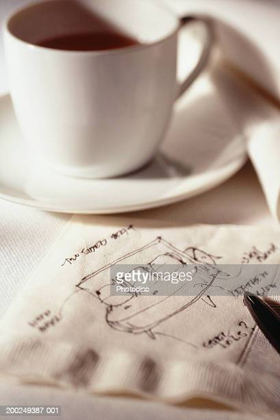 Cup of coffee and drawing of sofa on napkin (Close-up)