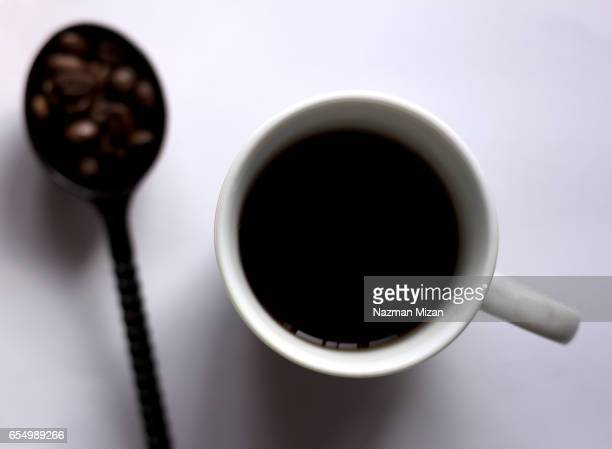 A cup of coffee and with beans in spoon on white background.