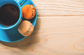 Top view. Mug with dark beverage and little cakes are on small round blue plate