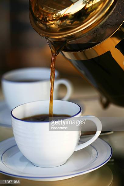 A cup of coffee being poured at a restaurant