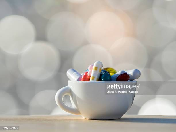 Cup of coffee  fills of medicines, tablets and pills