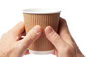 Carton cup of coffee in two human hands on white.