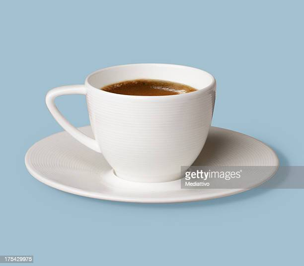 Cup of coffee in white mug on a white plate against blue