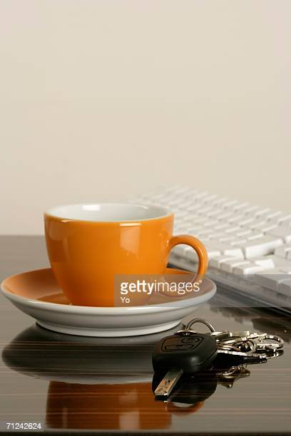Cup of coffee, keyboard and a car key on a table