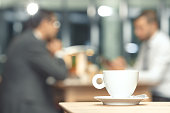 Cup of coffee on a table with a business partners in the background