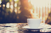 Hot coffee on old wood table with blur background of sunlight shining through the trees - soft focus, vintage tone
