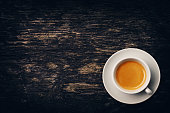 A cup of espresso coffee on weathered dark brown wood table.  coffee has a rich dark begie froth. A wood grain pattern of table featuring even grains of wood running horizontally across the image. The
