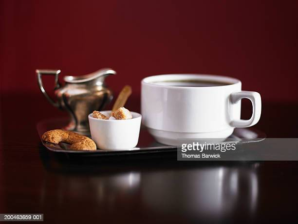 Cup of coffee, pitcher of cream, raw sugar cubes and cookies on tray