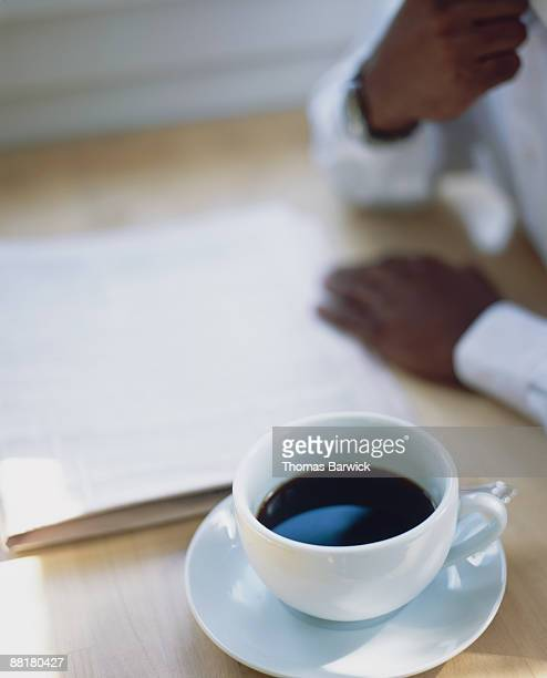 Cup of coffee sitting next to person reading