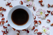 Cup of hot coffee with colorful beans, Phaseolus vulgaris,  and apple blossoms, Malus, on the table. Flat lay, top view.