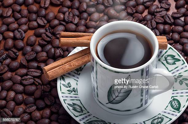 Cup of coffee with cinnamon and coffee beans
