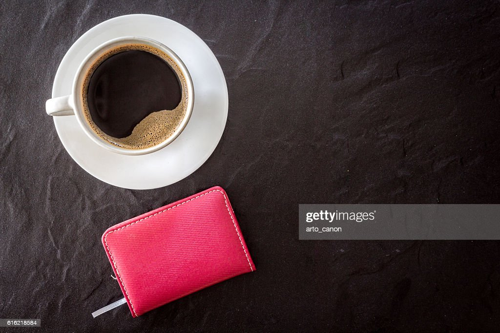 Cup of coffee with notebook on black background : Stock Photo
