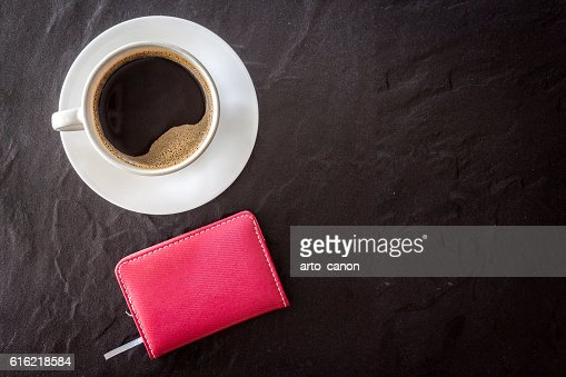 Cup of coffee with notebook on black background : Photo