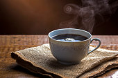 Cup of Steamy Coffee with smoke on wooden table