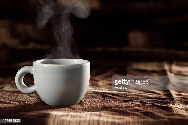 Cup of coffee with steam on brown tablecloth