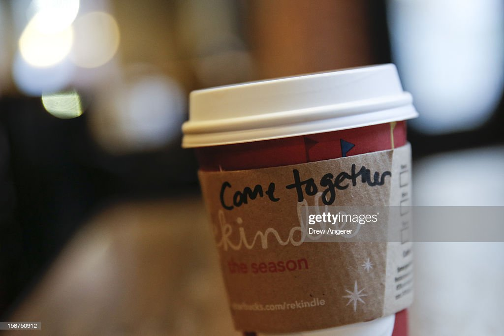 A cup of coffee with the words 'come together' written on the cup sits on the counter at Starbucks, on December 27, 2012 in Washington, DC. Starbucks CEO Howard Schultz says the words are intended as a message to lawmakers about the damage being caused by the divisive negotiations over the 'fiscal cliff.'
