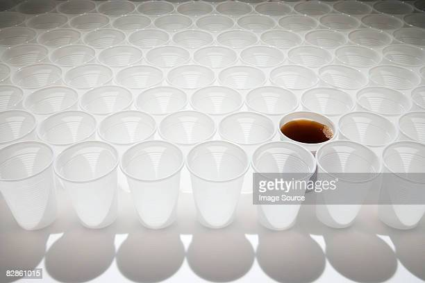 Cup of cola amongst empty cups