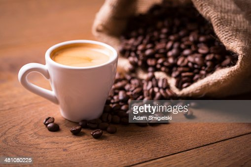 cup of espresso shot with coffee beans on wooden table
