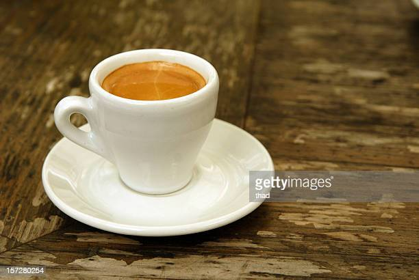 A cup of espresso sitting a white saucer