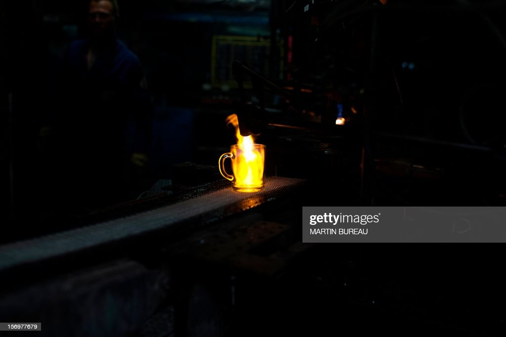 A cup of French manufacturer of glassware Duralex are seen on a production line, on November 26, 2012 at the factory in La Chapelle-Saint-Mesmin. AFP PHOTO MARTIN BUREAU