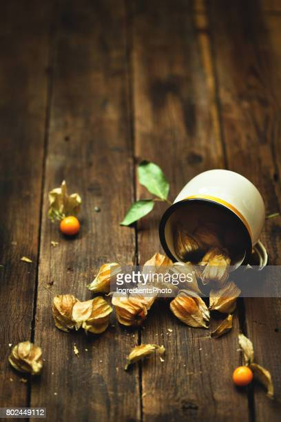 Cup of fresh delicious physalis on a wooden table.